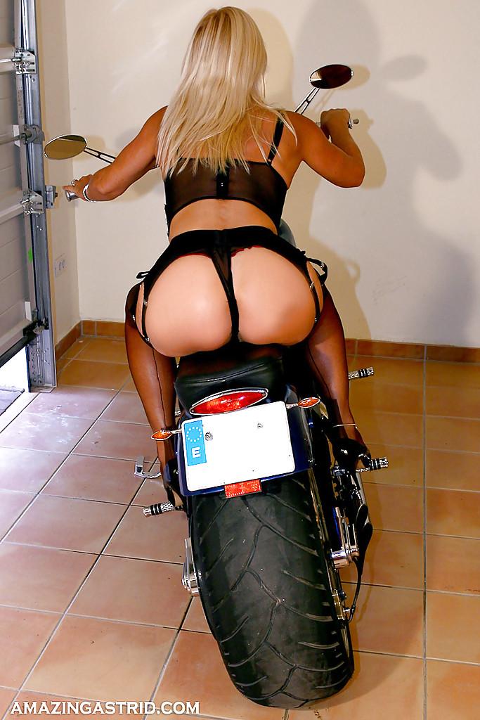 Зрелая блондинка позирует на мотоцикле