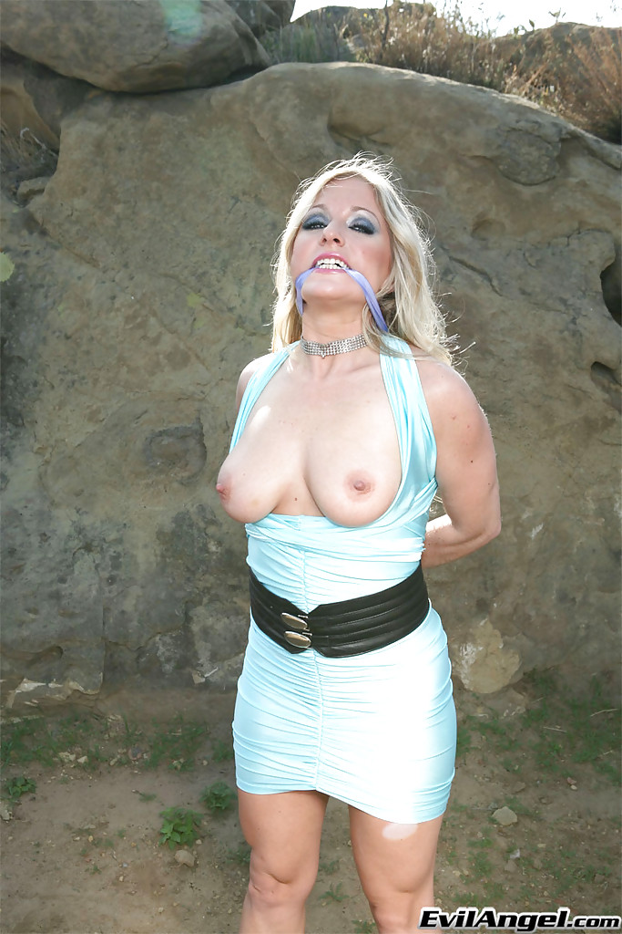 Матерая блонда позирует с голой киской и связанными руками