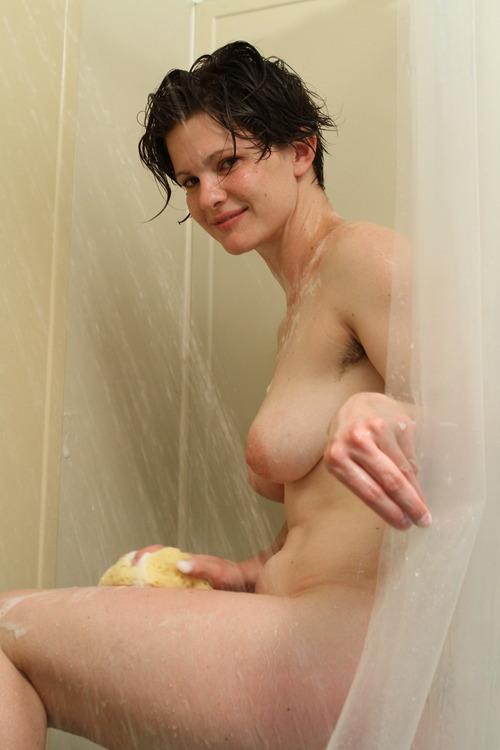 Очаровательная брюнетка купается в душе