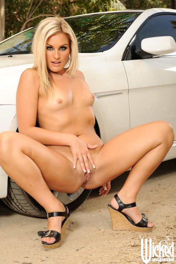 Блонда сверкает сочной пилоткой у автомобиля