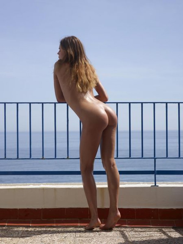Загоревшая милашка голышом любуется океаном