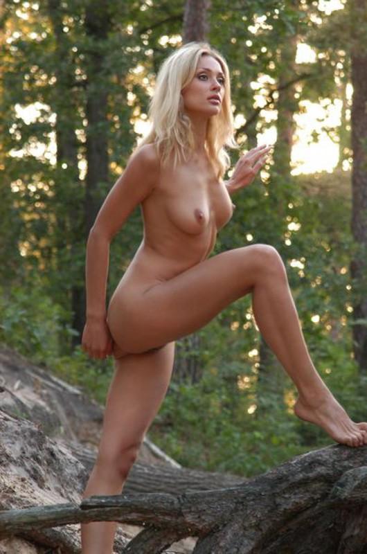 Лесная нимфа позирует нагая у старого дерева